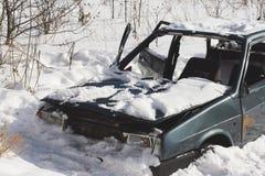 Coche destruido abandonado en la nieve Esqueleto del tra innecesario Imágenes de archivo libres de regalías