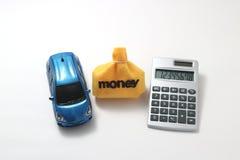 Coche, dinero, y calculadora del juguete Foto de archivo