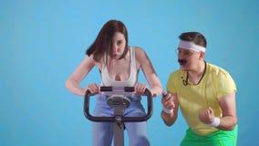 Coche divertido del hombre de años 80 con los trenes del bigote una mujer joven en la bicicleta estática en un fondo azul almacen de metraje de vídeo
