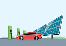 Coche eléctrico que carga en la estación de carga delante de los paneles solares
