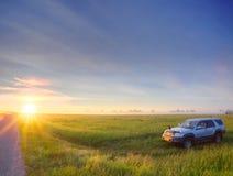 Coche en campo en puesta del sol Imagenes de archivo