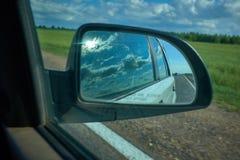 Coche en el camino con el fondo de la falta de definici?n de movimiento y el espejo de la vista posterior concepto del recorrido  foto de archivo libre de regalías