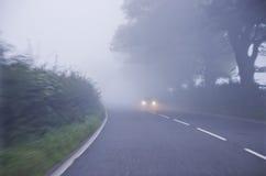 Coche en el camino en la niebla Autumn Landscape Fotos de archivo