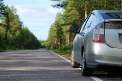 Coche en el camino finlandés en el bosque Foto de archivo