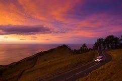 Coche en el camino en la puesta del sol, soporte Jaizkibel de la montaña Fotos de archivo libres de regalías