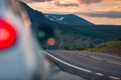 Coche en el camino en Noruega, Europa Viaje de la puesta del sol Foto de archivo libre de regalías