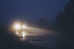 Coche en el camino sucio en niebla fuerte de la neblina en el crepúsculo Fotos de archivo
