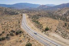 Coche en el camino vacío del desierto de Mojave Fotografía de archivo