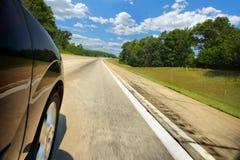 Coche en la autopista en un día asoleado Imagenes de archivo