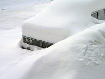 Coche en la nieve acumulada por la ventisca Fotos de archivo