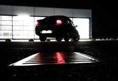 Coche en la noche, visión inferior desde la superficie de la carretera imagenes de archivo