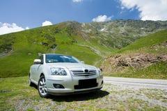 Coche estacionado cerca de un camino a través de las montañas Imagen de archivo