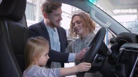 Coche familiar de compra, muchacha del pequeño niño detrás de la rueda del nuevo auto así como padres mientras que automóvil de l almacen de video