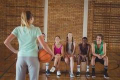 Coche femenino que se coloca con baloncesto en cancha de básquet Imagen de archivo