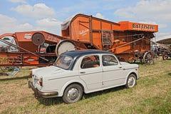 Coche Fiat 1100 del vintage cerca a una máquina vieja de la trilladora fotografía de archivo