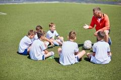 Coche Instructing Football Team en campo Imagen de archivo