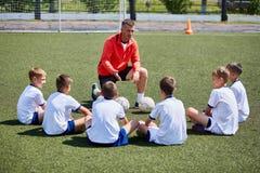 Coche Instructing Junior Football Team en la práctica Imagen de archivo libre de regalías
