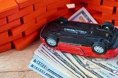 Coche invertido en la pila de billetes de dólar Concepto del seguro de coche, daños después del accidente fotografía de archivo