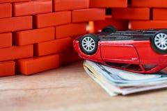 Coche invertido en la pila de billetes de dólar Concepto del seguro de coche, daños después del accidente fotos de archivo