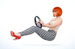 Coche joven del conductor de la muchacha del pelirrojo con el volante, concepto auto Foto de archivo libre de regalías