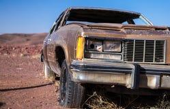 Coche marrón viejo con una linterna y un neumático desinflado reventados en el desierto debajo de un cielo azul Foto de archivo libre de regalías