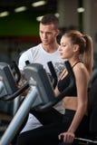 Coche masculino joven con el cliente femenino en gimnasio Foto de archivo