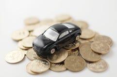 Coche miniatura del juguete en la pila de dinero Foto de archivo libre de regalías