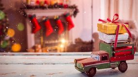 Coche modelo con los regalos de Navidad en su tejado en una sala de estar adornada para la Navidad combinada con almacen de video