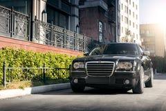 Coche negro Chrysler 300c que se coloca en la carretera de asfalto en la ciudad en el d3ia Foto de archivo libre de regalías