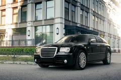 Coche negro Chrysler 300c que se coloca en la carretera de asfalto en la ciudad en el d3ia Fotos de archivo libres de regalías