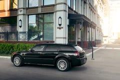 Coche negro Chrysler 300c que se coloca en la carretera de asfalto en la ciudad en el d3ia Imagen de archivo