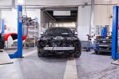 Coche negro desmontado en el taller cerca de los coches de la elevación preparados para la reparación: parte frontal, capilla y t imagen de archivo libre de regalías