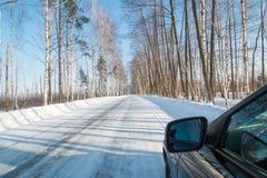 Coche negro en un camino nevoso del invierno en un bosque del abedul Imágenes de archivo libres de regalías