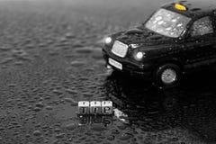 Coche negro tradicional británico del juguete del taxi del taxi con la extremidad de la palabra en gotas Fotos de archivo