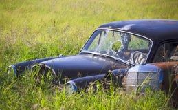 Coche oxidado en la hierba alta Foto de archivo libre de regalías