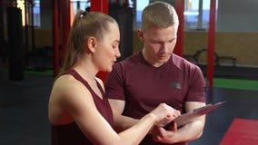 Coche personal muscular que escribe en el tablero y que habla con la mujer joven en gimnasio del entrenamiento cruzado metrajes