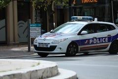 Coche policía francés que conduce rápidamente en el centro de ciudad de Menton Fran foto de archivo