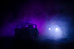 Coche policía que persigue un coche en la noche con el fondo de la niebla Coche policía de 911 respuestas de emergencia que apres Foto de archivo libre de regalías