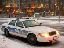 Coche policía estacionado en la noche en nevadas Imagen de archivo