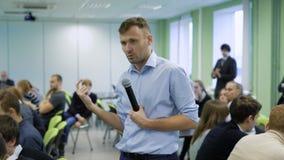 Coche profesional en la camisa azul que habla en el micrófono y que gesticula en el taller para los encargados superiores futuros metrajes