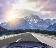 Coche que apresura en el autobahn entre paisaje de la montaña Fotos de archivo