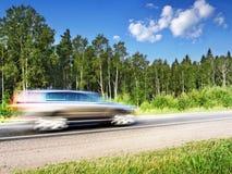 Coche que apresura en la carretera del país, falta de definición de movimiento Imagen de archivo libre de regalías