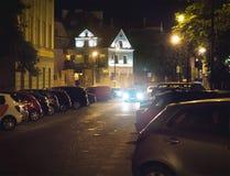 Coche que busca el espacio de estacionamiento libre en la noche en centro de ciudad o de pueblo Vehículo que intenta encontrar el Foto de archivo