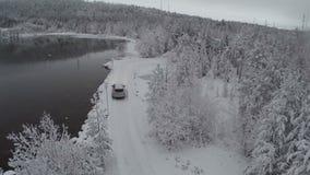 Coche que consigue a la reconstrucción a través de la madera de pino, visión aérea del invierno metrajes