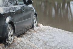 Coche que pasa a través de la inundación Fotos de archivo