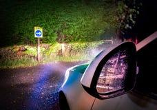 Coche que sale del lugar en la noche con las luces que brillan en muestra de la salida fotografía de archivo