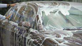 Coche que se lava del conductor masculino en el carwash costoso, negocio del automóvil, auto de lujo almacen de metraje de vídeo