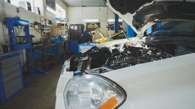Coche que se prepara para reparar - taller mecánico del garaje, pequeña empresa fotos de archivo