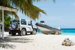 Coche que transporta la motora en la playa africana imagen de archivo