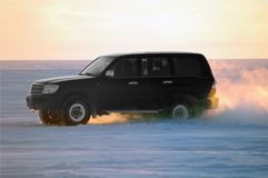 Coche que un vehículo a campo través monta en un lago sitiado por la nieve Fotos de archivo libres de regalías